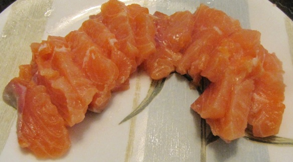 Cut salmon sashimi or cooked salmon into small pieces.