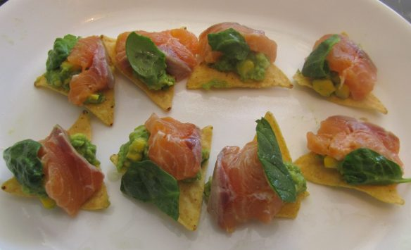 Add salmon pieces, guacamole, and spinach leaves to tortilla chips.