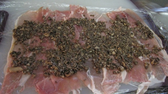Once the beef and mushrooms are done, begin to construct the wellington. Layer the ham on plastic wrap and spread out the mushrooms on top. Make sure it is sturdy, as this will seal the wellington.