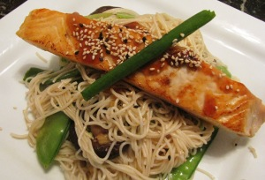Divide the noodles and vegetables between 2 serving plates. Top with the salmon. Sprinkle on the sesame seeds, and pour the remaining teriyaki sauce over the salmon. Done!